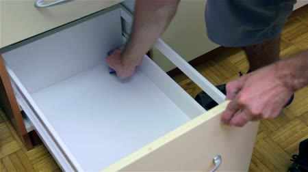 drawer : Cleaning drawer with sponge. Young attractive man in new home, checking and cleaning kitchen before using with own dishes. Stock Footage
