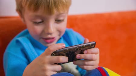 eszköz : Enthusiastic typing on smartphone. New technology using mobile telephone as play device for games and forget to go outside on playground with friends. Stock mozgókép