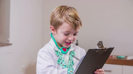 pomocník : Doctor kid writing report to patient. Young boy playing medical staff in clinic with stethoscope around neck and writing report in slow motion. Dostupné videozáznamy