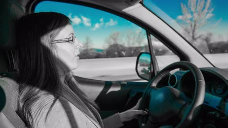 csak a nők : Driving car in black and white with blue tint. Inside car shot of woman driving on highway, colorless video only blue color of sky. Stock mozgókép
