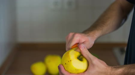 vágás : Removing peel from yellow apple. Person peeling sweet yellow apple with ceramic sharp knife from top to bottom. Stock mozgókép