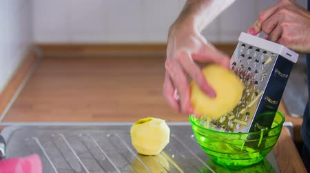 slicer : Pick up peeled apple and grate. Person in kitchen preparing sweet dish from peeled apples grated with kitchenware tool.