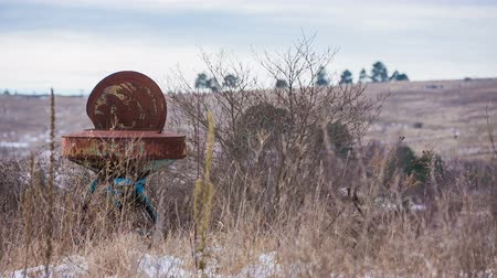maquinaria : Empty landscape with rusty old farm device. Old farm equipment in tall field grass in bad weather abandoned in wind.