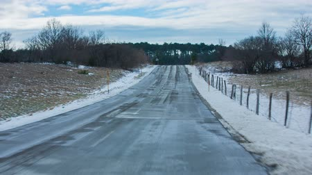 straight road : Driving through countryside in winter. Personal view from car while driving on wet road in winter time with no one anywhere. Stock Footage