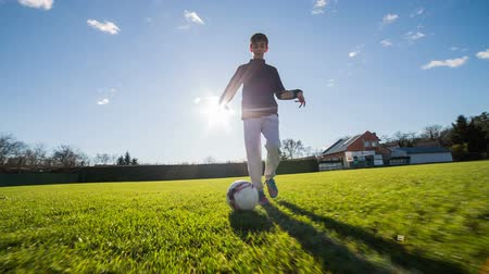 детеныш : Boy dribble soccer ball. Running in front of person dribble and kick soccer ball with sun shining in background and blue sky.