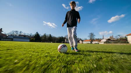Young kid dribbling soccer ball tracking shot. Soccer player dribble camera on green field. Stock Footage