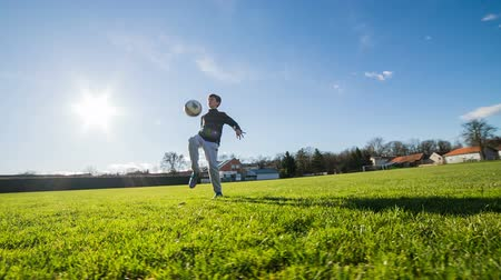 jogadores : Boy learn juggling soccer ball outdoor. Playing with soccer ball on big green soccer field on a sunny fresh day. Beautiful contrast image with green and blue.