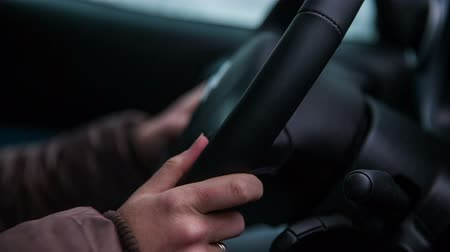 doğru : Womans hands holding steering wheel. Close up of hands holding steering wheel while driving in a bumpy ride.