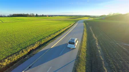 運輸 : Aerial of white car driving with blinkers on 4K. Flying from behind vehicle slowly driving on countryside road with sunset shining and another vehicle overtaking.
