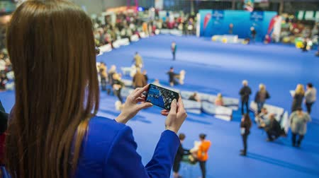авиашоу : Person video recording event with phone. Behind the shoulder view of person smartphone while recording dog show exhibition.