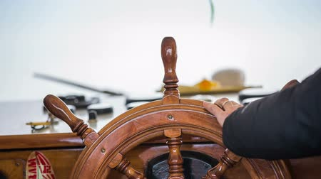 námořník : Steering rudder on a ship close up. Person controlling ship travel with wooden steering wheel made from bright wood.