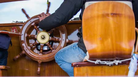námořník : Ship control steering wheel. Person sit on chair and controlling ship direction with wooden steering wheel made from bright wood.