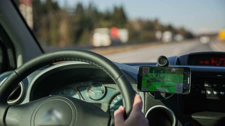 subir : Driving with navigation map. Close up on steering wheel in car with navigation GPS device beside showing route to goal. Driving on highway on a sunny day. Vídeos