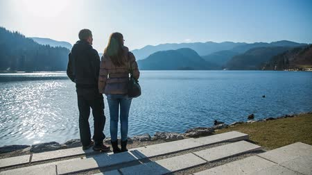 odrážející : Two person enjoy lake Bled view on sunny day. Young couple stand on lake edge and observe beautiful scene of blue lake on a sunny day. Clear blue sky. Dostupné videozáznamy