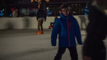 aktywność : Young boy skating in rink at night. Kid enjoying outdoor activity on ice surface at night, a lot of people skating as well. Wideo