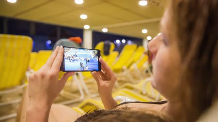 assistindo : Watching video on smartphone. Female person laying on deckchair at indoor pool complex and watching video.