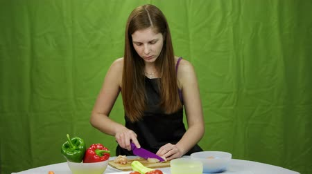 kahverengi : Woman chef cutting chicken meat. Brown hair woman cook cutting through white chicken on wooden cutting board with ceramic knife on green background