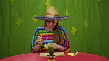 meksika : Girl in Mexican clothes eating dish. Attractive woman with big sombrero and colorful dress eating dish from bowl. Funny looking cactus on table.