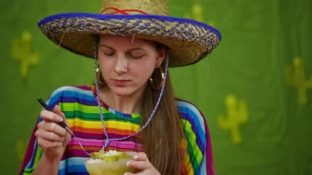 шляпа : Girl in Mexican suit eating rice and vegetables. Attractive woman with sombrero and colorful dress eating dish from small bowl, looking in to camera. Стоковые видеозаписи