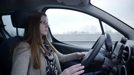 drive : Female person steering car inside shot 4K. Wide shot inside car vehicle on highway steering wheel, woman wearing sight glasses. Cars passing by. Stock Footage