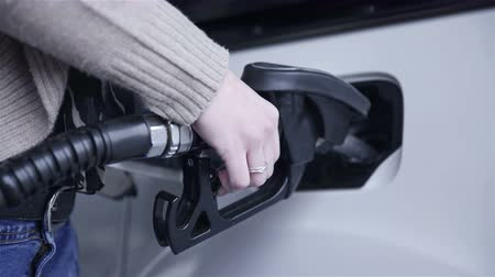 petrol : Person holding gasoline handle in car 4K. Female person fueling up empty car tank with diesel close up. Stock Footage