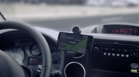 přístrojová deska : GPS navigation on smartphone showing route 4K. Close up on navigation screen tracking vehicle location and route while driving on road.