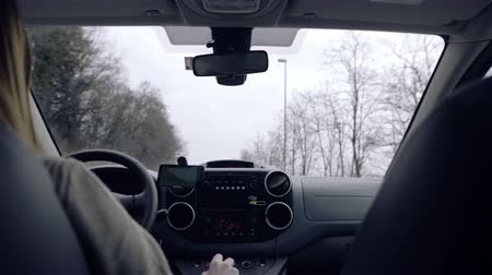 inside car : Car windshield from backseats while driving 4K. Wide shot of female person driving car vehicle through countryside, view from seats behind.