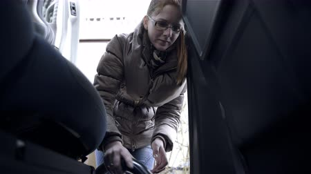 mycie rąk : Woman vacuuming between seats low angle 4K. Low angle medium shot view of attractive young woman cleaning inside car with vacuum cleaner. Dressed in warm jacket. Wideo