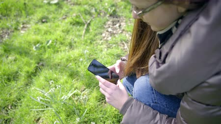 ajoelhado : Woman with smartphone over green glade 4K. Young female person kneeling over green glade with some snowdrops growing, preparing smartphone to take picture, over shoulder jib shot on a sunny day.