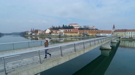 mocný : Woman walk on big bridge over river aerial shot 4K. Flying away from female person while walking on the other side of bridge. Bad weather. Ptuj city in background.