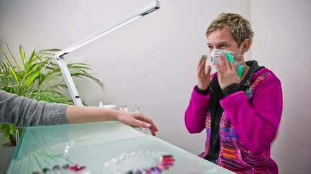 положить : Female manicurist puts up mouth mask before grinding. Professional person protects mouth and nose respiratory tract against nail particles when grinding customer fingernails.