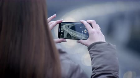 стрельба : Photographing famous highway viaduct 4K. Female person holding smartphone mobile device making pictures of big half circle viaduct in Slovenia.