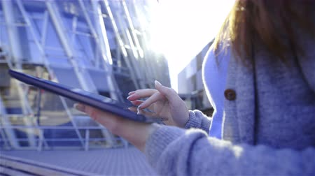 nehet : Female person with long polished nails holding big tablet computer making gestures on screen outside in front business buildings..Sliding over tablet-computer with futuristic buildings in background 4K