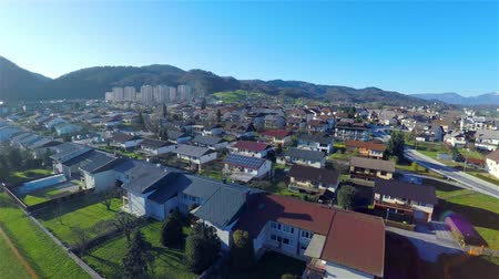 yerleşim : Aerial shot of many houses and few apartment blocks in the distance. Almost sunset with hills far in background..Ascending over town at sunset 4K