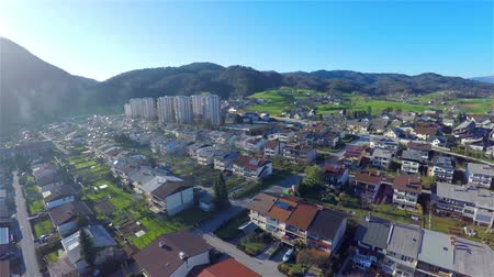 yerleşim : Aerial shot of many houses and few apartment blocks in the distance. Almost sunset with hills far in background..Backward flying over settlement of houses 4K