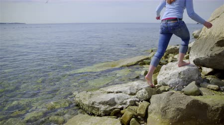 treading : Walk on sea rocks and lean to sunbath 4K. Woman in blue sweater and jeans tries temperature of water and walks on rocks barefoot to sunbath leaning on huge rock. Stock Footage