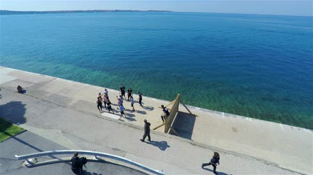 slovinsko : Athletes jumping over wooden wall at sea 4K AERIAL. Flying over the seaside with people running and climbing over wooden barrier with view on seascape on a sunny day.