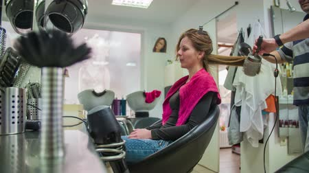 cabelos grisalhos : Man combing and drying hair at salon 4K. Family man running hairdresser salon, taking care of young happy female customer.