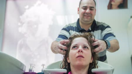 şampuan : Person rubbing woman hair at salon low angle 4K. Male hairdresser rubbing customer head and hair before the trimming. Having a chat with woman.