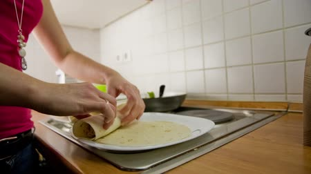 mexicaans : Persoon in de keuken keuken Mexicaanse tortilla Taquito schotel. Persoon preparing traditioneel Mexicaans Taquito gerecht uit tortilla met vlees en groenten binnen. Rolling elkaar en de invoering van bakplaat kraan schot.