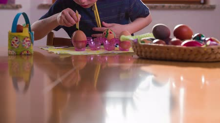 koszyk wielkanocny : Table reflection of boy coloring Easter eggs 4K. Sliding over brown table with reflection of child painting on eggs for Easter holiday in slow motion. Wideo