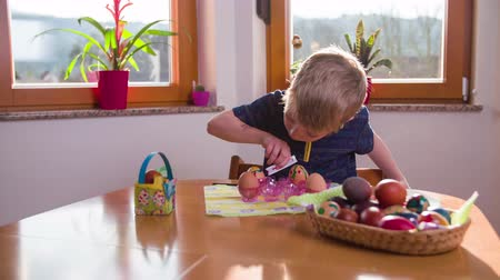 ovo : Kid carefully adding lines to egg 4K. Cute blonde hair boy in kitchen with big brown table and windows in background working drawing decorations on eggs for Easter holiday.
