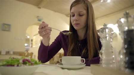 comer : Woman slowly eating delicious soup at restaurant 4K. Low angle of long brown hair female person holding spoon and eating soup from white bowl on table. Alone in restaurant.