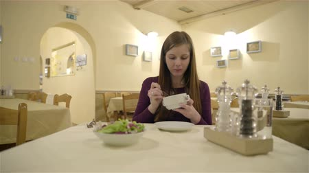 eat background : Young woman at restaurant eating dish 4K. Wide shot of woman alone at empty nice looking restaurant eating dinner, holding bowl with soup. Female person with long brown hair.
