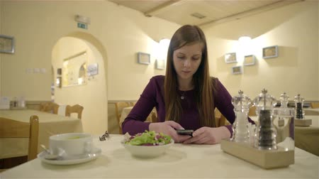 unott : Typing message on phone while at restaurant 4K. Attractive young woman with brown hair eating lunch at restaurant waiting for someone typing a message on smartphone. Worried expression.
