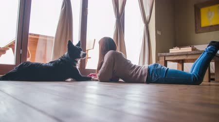 curiosidade : Dog and female person lay on floor caressing 4K. Wide low angle view of living room and owner with dog together on domestic floor looking each other. Big terrace windows in background.