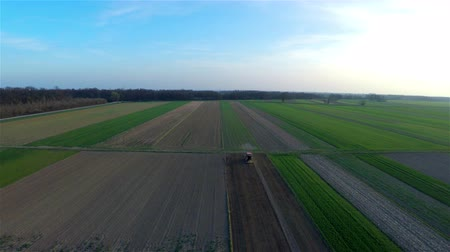 talaj : Flying backwards over farm fields at sunset 4K. Many farm fields growing different vegetables. One tractor plowing on very narrow fresh soil. Aerial view.