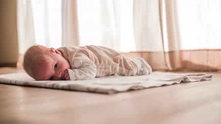 cobertor : Baby rest on floor blanket 4K. Low angle of newborn cute baby laying on stomach on wooden floor in front of window curtains.