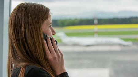podróżnik : Person make a call at airport. Woman with long brown hair on a phone while waiting on airport. Plane in background parked. Wideo
