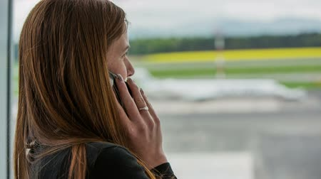 očekával : Typing on phone and call for transportation. Woman wait at airport and make a call for transportation. Standing next to window with airplane outside parked. Dostupné videozáznamy